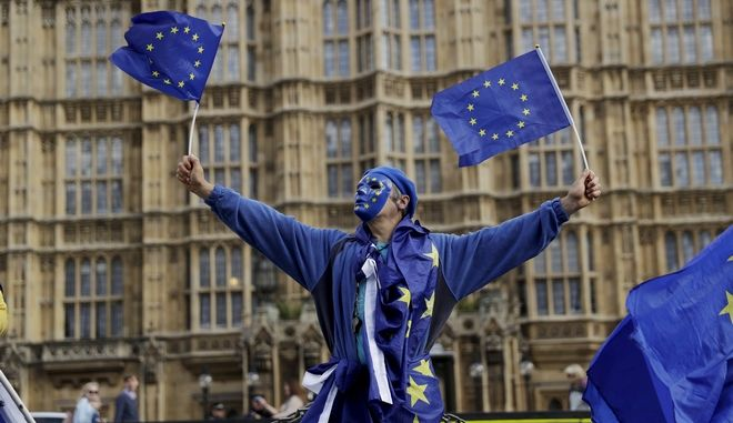 A pro-remain supporter of Britain staying in the EU, wears an EU flag mask whilst taking part in an anti-Brexit protest outside the Houses of Parliament in London, Monday, Sept. 11, 2017. Lawmakers are due to vote late Monday or early Tuesday on the European Union (Withdrawal) Bill, which aims to convert around 12,000 EU laws and regulations into domestic statute on the day the country leaves the bloc in March 2019. (AP Photo/Matt Dunham)
