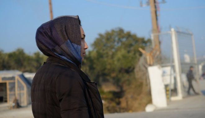 A refugee woman stands outside the Moria refugee camp on the northeastern Greek island of Lesbos, on Friday, Nov. 25, 2016. Police say two people have died on Lesbos and two others were seriously injured after a fire raged through a refugee camp used for migrants facing deportation back to Turkey. (AP Photo/Lefteris Pitarakis)