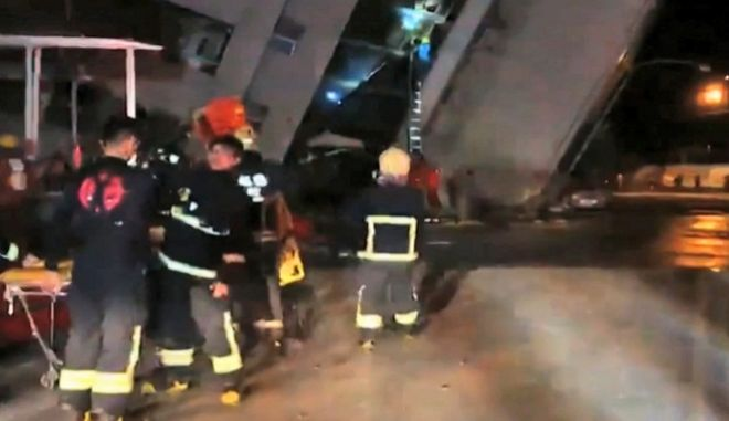 In this image from TV, emergency services attend after a building collapsed on its side, as a man climbs a ladder to gain access to the building, centre background, after an early morning earthquake in Hualien County, eastern Taiwan, early Wednesday, Feb. 7 2018.  A magnitude-6.4 earthquake struck late Tuesday near the coast of Taiwan, and people may be trapped inside the building. (EBC via AP)