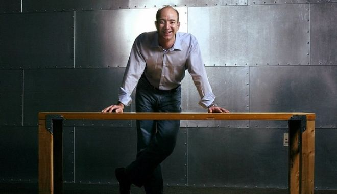Jeff Bezos, founder, CEO and chairman of Amazon.com, stands with one of the company's trademark door-desks at the company's Seattle headquarters, Thursday, March 11, 2004. A decade after its founding, the Internet retailing giant has experienced more dizzying ups and downs than most companies experience in decades of doing business. Bezos says it's still way too early to say whether Amazon is getting close to a phase that could be called business as usual. (AP Photo/Andy Rogers)
