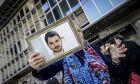 Συγγενείς του Μάριου Παπαγεωργίου κρατώντας πλακάτ και φωτογραφίες