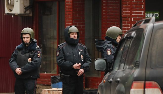 Police officers block access to a candy factory where the former owner killed a security guard and injured three people in Moscow, Russia, Wednesday, Dec. 27, 2017. The Russian Investigative Committee says the man argued with the factory's new owner and then opened fire with a shotgun. (AP Photo/Pavel Golovkin)