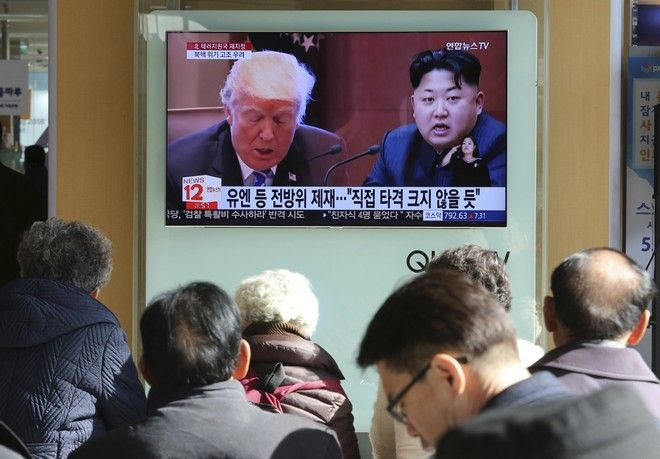 """FILE- In this Tuesday, Nov. 21, 2017, file photo, people watch a TV screen showing images of U.S. President Donald Trump, left, and North Korean leader Kim Jong Un at Seoul Railway Station in Seoul, South Korea. North Korea has called U.S. President Donald Trump's decision to relist the country as a state sponsor of terrorism a """"serious provocation"""" that justifies its development of nuclear weapons. (AP Photo/Ahn Young-joon, File)"""