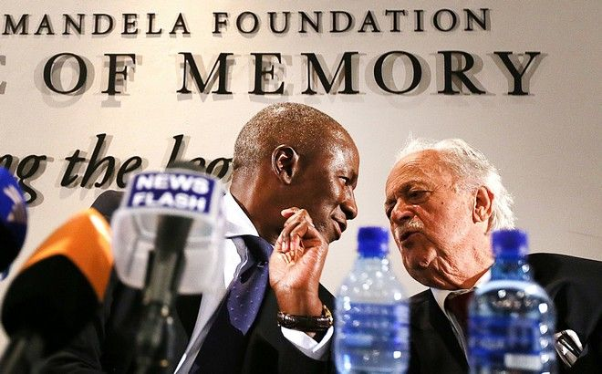 South Africa's deputy chief justice Dikgang Moseneke, left, chats with Advocate George Bizos, right, during their media briefing after a will was read in its entirety to members of Mandelas family at the Nelson Mandela Foundation in Johannesburg, South Africa, Feb. 3, 2014. The Nelson Mandela Foundation Nelson Mandela's estate is worth roughly $4.1 million, excluding royalties and other amounts, and beneficiaries of his will include his family, members of his staff, schools that he attended and the African National Congress, the movement that fought white rule and now governs South Africa, the will's executors said Monday. (AP Photo/STR)