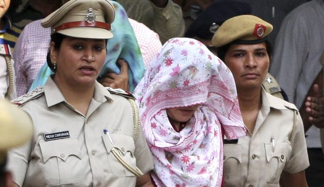 Honeypreet Insan, head covered with scarf, adopted daughter of flamboyant Indian spiritual guru who calls himself Dr. Saint Gurmeet Singh Ram Rahim Insan, leaves after being produced in court in Panchkula, India, Wednesday, Oct. 4, 2017. Earlier in August the guru was sentenced to a total of 20 years in prison on charges of raping two female followers. Honeypreet was remanded to six days in police custody in connection with violent protests by the gurus followers after the conviction that left at least 38 people dead and hundreds injured. (AP Photo/Kapil Sethi)
