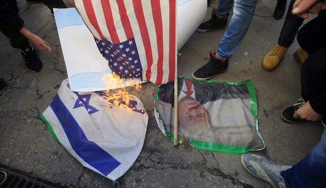 Lebanese and Palestinians students, burn a picture of U S. President Donald Trump, an American flag and an Israeli flag, as they take part in a protest at the Lebanese University, in the southern port city of Sidon, Lebanon, Thursday, Dec. 7, 2017, against U.S. President Donald Trump's decisions to recognize Jerusalem as the capital of Israel. (AP Photo/Mohammed Zaatari)
