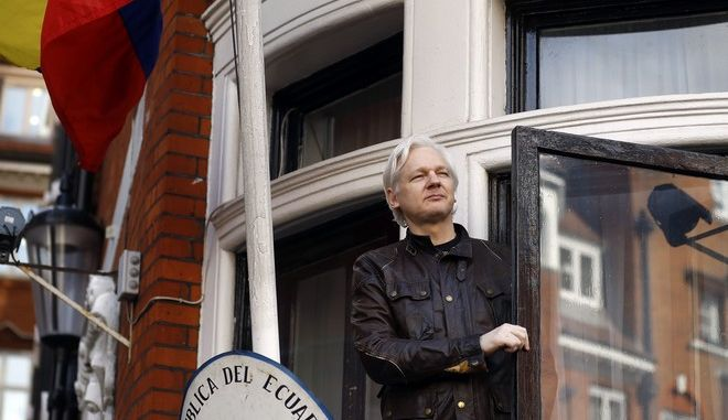 FILE- In this Friday May 19, 2017 file photo, WikiLeaks founder Julian Assange greets supporters outside the Ecuadorian embassy in London. Britain's Foreign Office said Thursday, Jan. 11, 2018 it has rejected Ecuador's request to grant diplomatic status to Assange, who has been living in the nation's embassy in London since 2012 to avoid arrest by U.K. authorities. (AP Photo/Frank Augstein, File)