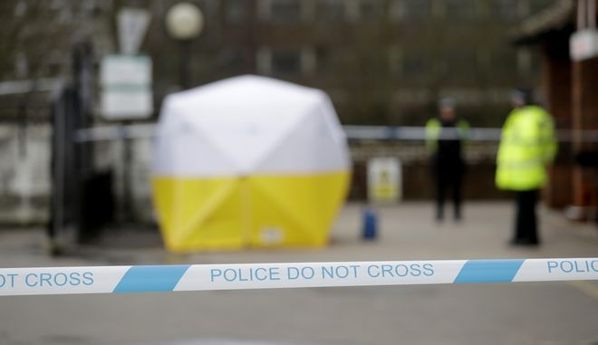 "Police officers guard a cordon around a police tent covering a supermarket car park pay machine near the spot where former Russian double agent Sergei Skripal and his daughter were found critically ill following exposure to the Russian-developed nerve agent Novichok in Salisbury, England, Tuesday, March 13, 2018. The use of Russian-developed nerve agent Novichok to poison ex-spy Sergei Skripal and his daughter makes it ""highly likely"" that Russia was involved, British Prime Minister Theresa May said Monday. Novichok refers to a class of nerve agents developed in the Soviet Union near the end of the Cold War. (AP Photo/Matt Dunham)"