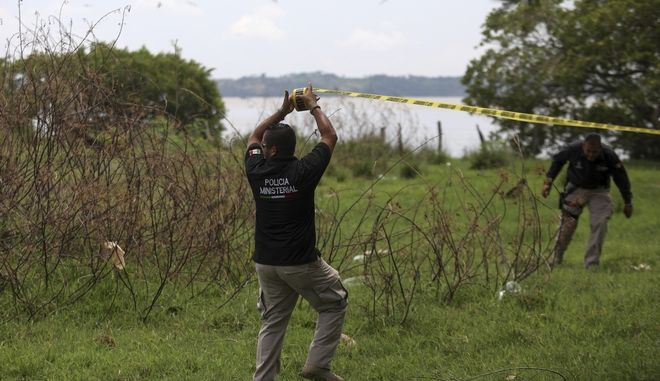 Police cordon off the area at a clandestine grave site in Arbolillo, Veracruz state, Mexico, Friday, Sept. 7, 2018. One day after authorities in the Mexican state of Veracruz announced the discovery of at least 166 skulls in mass graves, journalists who arrived at the site Friday discovered it was the same location where authorities said they had found 47 bodies the previous year. (AP Photo/Felix Marquez)