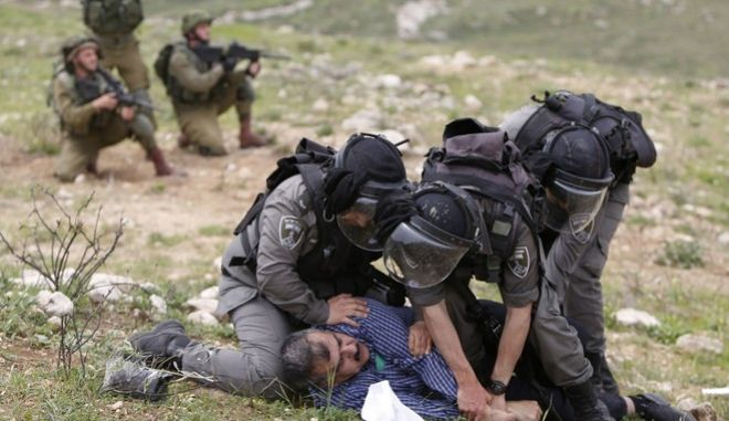 Israeli border police arrest a Palestinian during clashes following a protest to mark the Land Day near the village of Madama, south of the West Bank city of Nablus, Thursday, March 30, 2017. Land Day commemorates the killing of six Arab citizens of Israel by the Israeli army and police on March 30, 1976 during protests over Israeli confiscations of Arab land. (AP Photo/Majdi Mohammed)