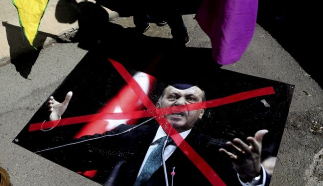 """A boy in silhouette holds a flag by a poster on the ground showing the Turkey's President Recep Tayyip Erdogan during a protest against the Turkish offensive targeting Kurds in Afrin, Syria, outside of the US embassy in Nicosia, Cyprus, on Monday, March 12, 2018. Kurds with images of the presidents of Turkey and Russian, shouted slogans as they marched on the Russian and US embassies to protest Turkey's """"invasion"""" of a Kurdish enclave in northern Syria. (AP Photo/Petros Karadjias)"""