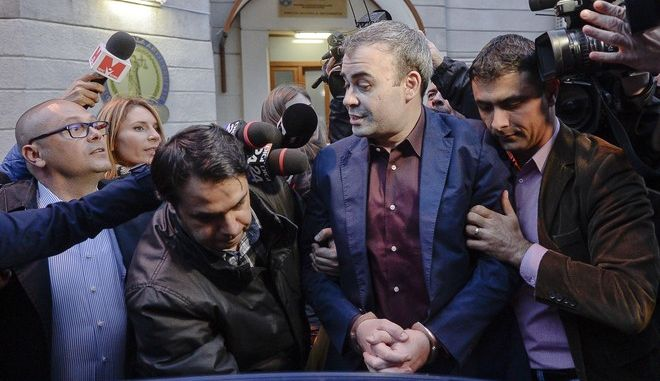 FILE - In this Wednesday, March 25, 2015 file photo, former Romanian finance minister Darius Valcov exits handcuffed from the prosecutors office in Bucharest, Romania. Former finance minister Darius Valcov is on trial for bribery, as prosecutors say he amassed a trove of paintings from illicitly gained wealth including artwork by Pablo Picasso and Andy Warhol to conceal the origin of money dishonestly gained. (Octav Ganea/Mediafax via AP, file)
