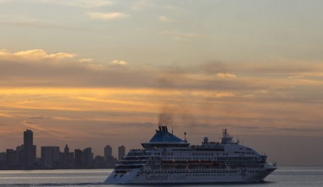 The Celestyal Crystal cruise ship departs Havana, Cuba, as the sun sets on Tuesday, Dec. 22, 2015. Cruise ships dock regularly in the port of Havana during the winter season, disgorging hundreds of travelers at a time into the adjacent colonial quarter. (AP Photo/Desmond Boylan)