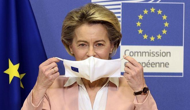 European Commission President Ursula Von Der Leyen puts on her face mask as she welcomes Moldova's President Maia Sandu prior their meeting at the European Commission headquarters in Brussels, Monday, Jan. 18, 2021. (Johanna Geron, Pool Photo via AP)
