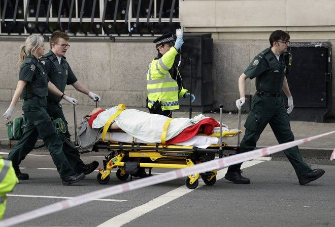 Emergency services transport an injured person to an ambulance, close to the Houses of Parliament in London, Wednesday, March 22, 2017. London police say they are treating a gun and knife incident at Britain's Parliament