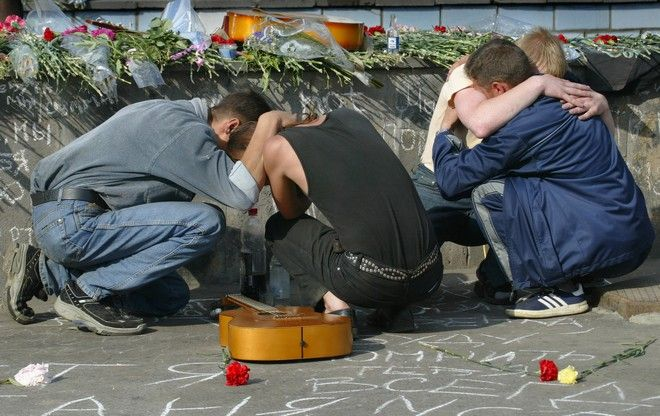 Alexander, no second name given, 22, rear right, cries embracing friends who also knew victims of Saturday's twin suicide bomber attacks on a rock festival at the attack site, in Moscow, Monday, July 7, 2003.  Alexander returned Monday to the scene of a  bombing a to leave flowers in memory of his girlfriend Kseniya who was killed in the attack. They were waiting to get in to the festival Saturday and  he left to buy a beer when the blast went off, returning to see Kseniya mortally wounded in the attack.  (AP Photo/Alexander Zemlianichenko)