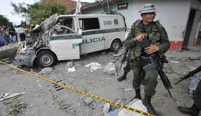 A police officer stands next to a police vehicle damaged during home made mortars attack to the police station in Villa Rica, southwest Colombia, Thursday, Feb. 2, 2012. The police post's commander and at least five civilians died during the attack, that came a day after a bomb in the Pacific port of Tumaco killed nine people. (AP Photo/Carlos Julio Martinez)