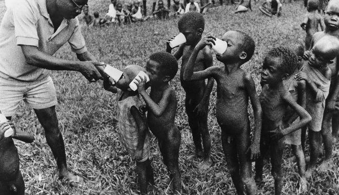 Γιατρός δίνει γάλα σε υποσιτισμένα παιδιά