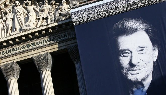 A giant poster of late French rock star Johnny Hallyday hangs on the facade of the Madeleine church in Paris, Saturday, Dec.9, 2017. France is bidding farewell to its biggest rock star, honoring Johnny Hallyday with an exceptional funeral procession down the Champs-Elysees, a presidential speech and a motorcycle parade, all under intense security. (AP Photo/Francois Mori)