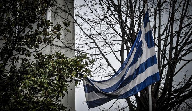 Ελληνική σημαία έχει μπλεχτεί σε καλδιά δέντρου εξαιτίας του αέρα έξω από κτήριο στην πόλη των Τρικάλων. (EUROKINISSI/ΘΑΝΑΣΗΣ ΚΑΛΛΙΑΡΑΣ)