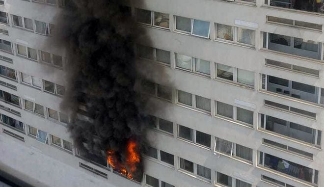 A fire burns in a 12th floor flat in a 22 storey high-rise tower block in east London, Friday June 29, 2018. (AP Photo/Umberto Campolongo)