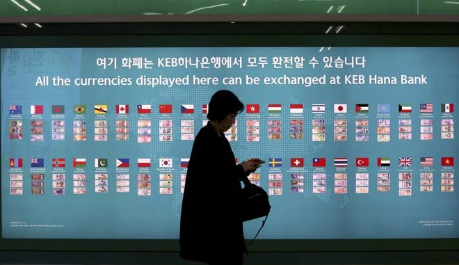 A woman walks by a board displaying various banknotes issued in the world at a subway station in Seoul, South Korea, Thursday, Oct. 19, 2017. South Korea's central bank says Asia's fourth-largest economy is likely to grow 3.0 percent this year, helped by strong exports. (AP Photo/Ahn Young-joon)