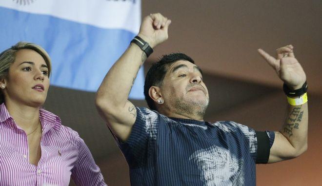 Argentinian soccer legend Diego Maradona cheers from the stands along with his partner Rocio Oliva during the Davis Cup finals tennis singles match between Argentina's Juan Martin Del Potro and Croatia's Marin Cilic in Zagreb, Croatia, Sunday, Nov. 27, 2016. (AP Photo/Darko Bandic)