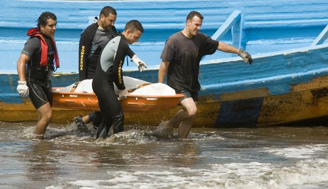 Rescue workers carry a stretcher with the body of a dead would be immigrant who arrived in a boat with 57 other to El Medano, on the Spanish Canary Island of Tenerife, Tuesday, July 17, 2007. Thousands of African immigrants arrive by boat every year trying to find a better life in Europe. (AP Photo/Arturo Rodriguez)