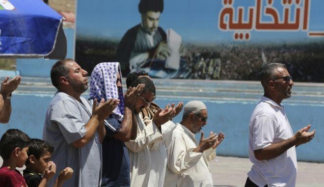 Υποστηρικτέςς του Σιίτη ιερωμένου Μουκταντά αλ-Σαντρ παρακολουθούν ανοιχτή προσευχή, μπροστά από προεκλογική αφίσα του στη Βαγδάτη