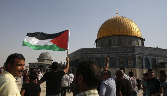Palestinians wave a flag near the Dome of the Rock Mosque in the Al Aqsa Mosque compound in Jerusalem's Old City Thursday, July 27, 2017. Israeli Prime Minister Benjamin Netanyahu has ordered police reinforcements deployed to Jerusalem following clashes at a flashpoint holy site. (AP Photo/Mahmoud Illean)