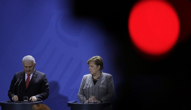 German Chancellor Angela Merkel, right, and Turkish Prime Minister Binali Yildirim stand behind the red light of a camera during a press conference after a meeting in the chancellery in Berlin, Germany, Thursday, Feb. 15, 2018. (AP Photo/Markus Schreiber)