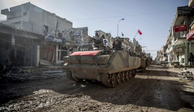 FILE - In this February 22, 2015, file photo, the Turkish army's armored vehicles and tanks drive in Syrian town of Ayn al-Arab, also known as Kobani, as they return from the Ottoman tomb in Syria. Turkeys military incursion in northern Syria succeeded in gaining it a foothold and driving Islamic State group militants away from its border _ but its determination to also push back the Kurds is causing it trouble. (AP Photo/Mursel Coban, Depo Photos, File)