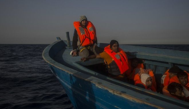 Refugees and migrants, mostly from Sudan and Bangladesh, wait to be assisted by an NGO aboard an overcrowded wooden boat, about 13 miles north of Sabratha, Libya, on Saturday, March 4, 2017. The rescue ship belonging to a Spanish NGO has saved 250 migrants in danger of capsizing near the Libyan coast on Saturday. Proactiva Open Arms spokesperson Laura Lanuza says that the NGO's boat rescued the African migrants from two small rubber vessels that were at risk of being overwhelmed by the sea. (AP Photo/Santi Palacios)