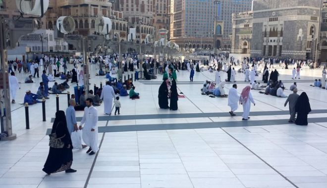 This Monday, Dec. 9, 2013 photo shows worshippers outside of the Grand Mosque in Mecca, Saudi Arabia. The Saudi society is governed by a mix of ancient customs and conservative interpretations of Islam. Most women cover their face and by law must wear long flowing black abayas in public. (AP Photo/Aya Batrawy)