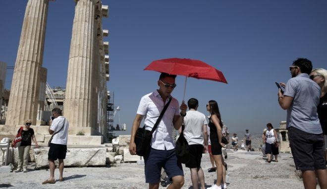 Τουρίστες περπατούν στον βράχο της Ακρόπολης (Φωτογραφία αρχείου)