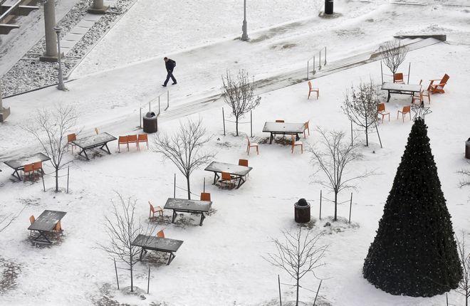 Άνδρας περπατά στη χιονισμένη πλατεία Barney Allis στο Κάνσας
