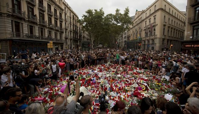 People pay respect at a memorial tribute of flowers, messages and candles to the victims on Barcelona's historic Las Ramblas promenade on the Joan Miro mosaic, embedded in the pavement where the van stopped after killing at least 13 people in Barcelona, Spain, Saturday, Aug. 19, 2017. (AP Photo/Emilio Morenatti)