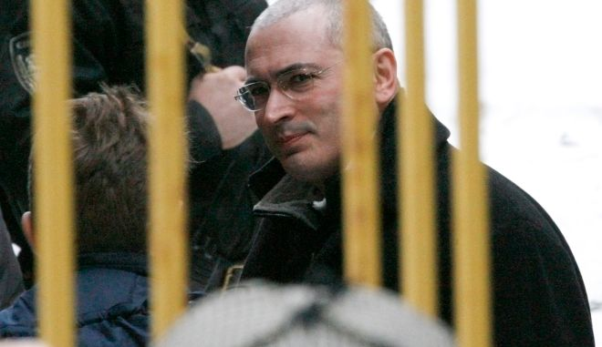 Handcuffed former Yukos chief Mikhail Khodorkovsky is led into a court building in Moscow March 3, 2009. Jailed Russian oil tycoon Mikhail Khodorkovsky arrived at a Moscow court on Tuesday at the start of a new trial for money laundering and embezzlement, a Reuters reporter at the courtroom said.  REUTERS/Sergei Karpukhin  (RUSSIA)