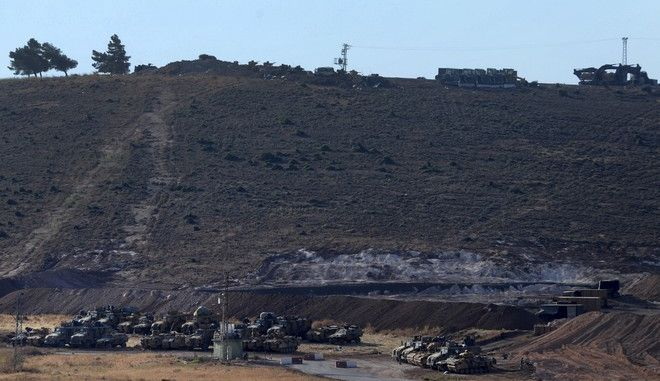 """Turkey's forces' tanks and vehicles hold positions close to the border with Syria, near the town of Reyhanli, Turkey, Monday, Oct. 9, 2017. Turkey's military said on Monday that Turkish troops moved into Syria's northwestern Idlib province the previous day as part of an operation to enforce a """"de-escalation"""" zone that was internationally agreed earlier this year. Also Sunday, Turkish forces shelled areas along the border in an area dominated by al-Qaida-linked militants in Syria. (Murat Kibritlioglu/DHA-Depo Photos via AP)"""