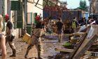Εργάτες μετακινούν έπιπλα από τον δρόμο μετά τις πλημμύρες στη Μαγιόρκα
