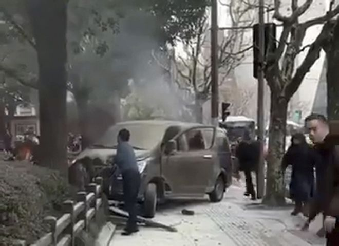 In this image taken from cellphone video provided to the Associated Press, a minivan involved in an accident rests on the sidewalk along a street in Shanghai, Friday, Feb. 2, 2018. A minivan plowed into pedestrians on a sidewalk in downtown Shanghai on Friday, sending more than a dozen people to hospitals. (AP Photo)