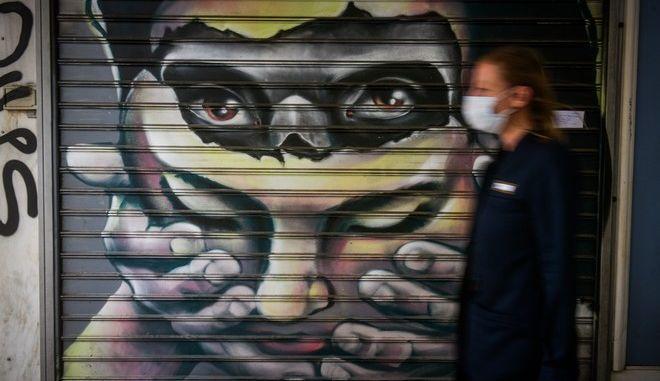 Γυναίκα με μάσκα περνά έξω από κλειστή επιχείρηση με καλλιτεχνικό γκράφιτι