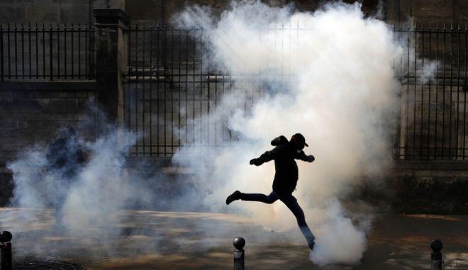 Διαδηλωτής στη Γαλλία κλωτσά καπνογόνο της αστυνομίας κατά τη διάρκεια απεργίας για τα τρένα στο Παρίσι