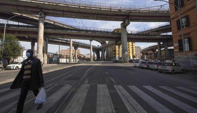 Άντρας περπατά σε άδεια λεωφόρο της Ρώμης