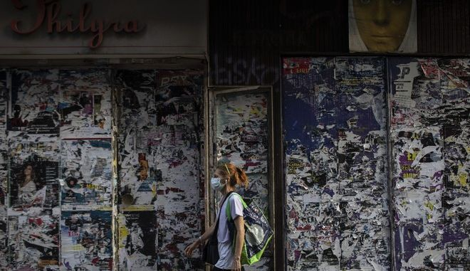 Γυναίκα με μάσκα μπροστά από κλειστό κατάστημα στην Αθήνα.