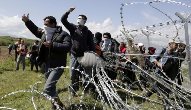 A group of migrant men call to others during protest at a fence at the northern Greek border point of Idomeni, Greece, Sunday, April 10, 2016. Thousands of migrants protested at the border and clashed with Macedonian police. (AP Photo/Amel Emric)