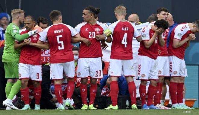 Οι ποδοσφαιριστές της Δανίας σχηματίζουν ένα τείχος ενώ το ιατρικό προσωπικό προσπαθεί να σώσει τη ζωή του συμπαίκτη τους, Κρίστιαν Έρικσεν