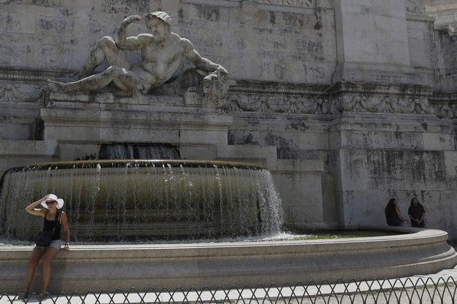 A woman sits near the Adriatic Sea Fountain in Rome, Thursday, Aug. 3, 2017. Italy's heat wave has pushed the mercury to levels as high as 40 degrees Celsius (104 Fahrenheit). (AP Photo/Gregorio Borgia)