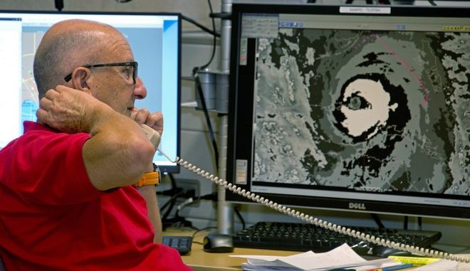 Senior Hurricane Specialist Lixion Avila, conducts the 5 p.m. Hurricane Irma forecast coordinating conference Saturday, Sept. 9, 2017, at the National Hurricane Center in Miami. At right, a video monitor displays an infrared image of Irma. (AP Photo/Andy Newman)