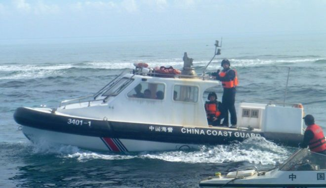In this Dec.24, 2015, photo provided by Renato Etac, Chinese Coast Guard members approach Filipino fishermen as they confront them off Scarborough Shoal at South China Sea, also called the West Philippine Sea, in northwestern Philippines. More than once, Chinese coast guardsmen approached Etac's boat and pointed their rifles at him, but he says he knew they would not fire and risk starting a war.(Renato Etac via AP)